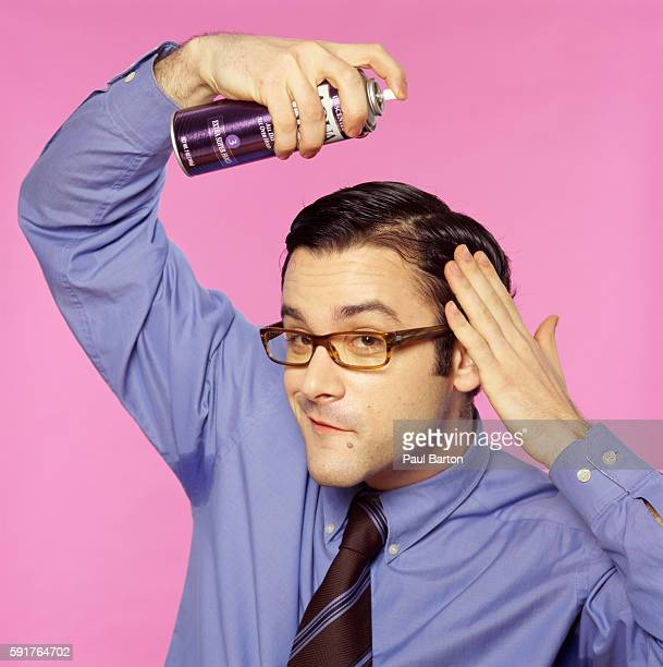 Man styling his hair with hairspray