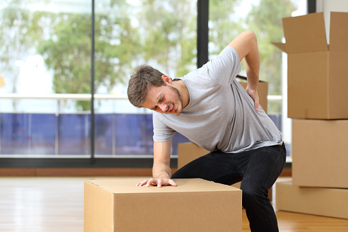 Man suffering back ache moving boxes 504461420