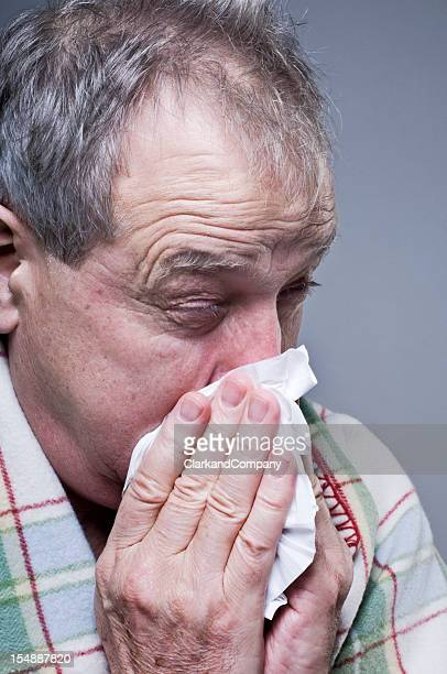 Man Suffering From A Cold Blowing His Nose