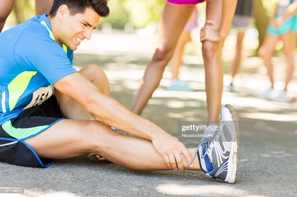 Man Suffering From Ankle Pain On Street During Marathon : Stock Photo
