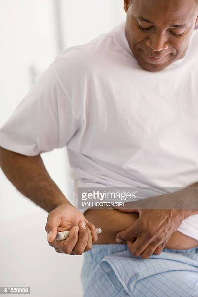 man suffering from diabetes injecting insulin on waist - insulin stock pictures, royalty-free photos & images