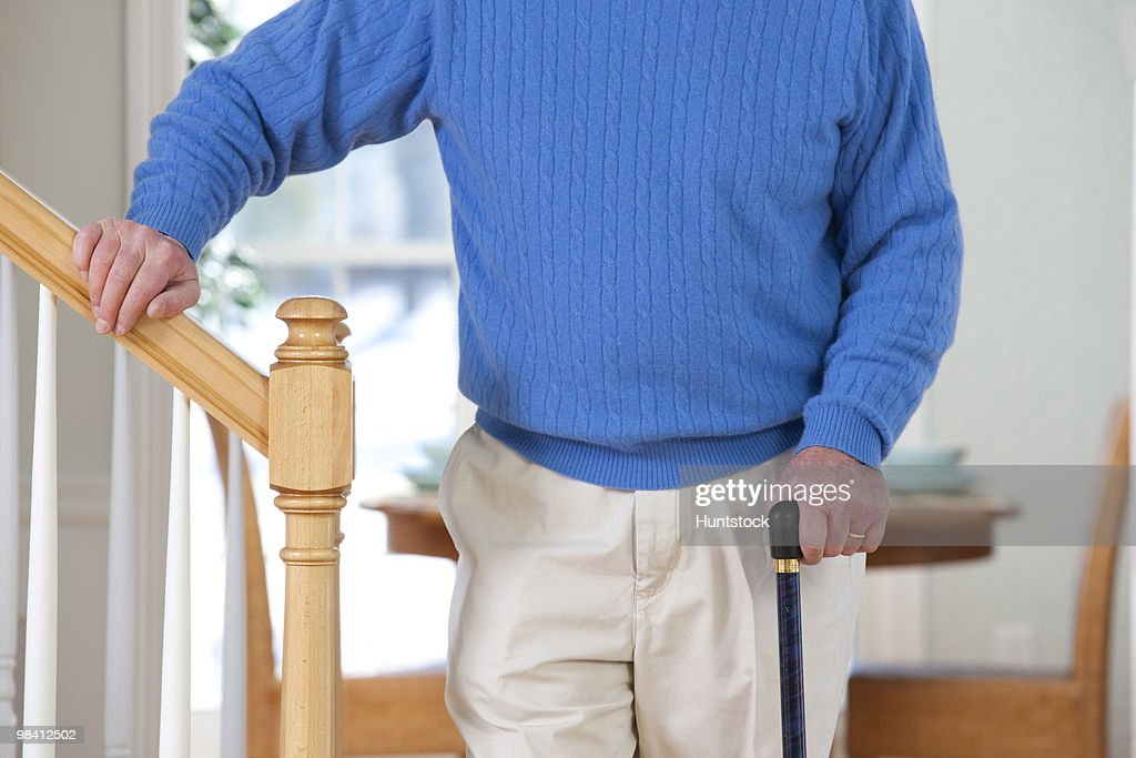 Man suffering from Parkinson's disease and multiple sclerosis standing near steps : Stock Photo