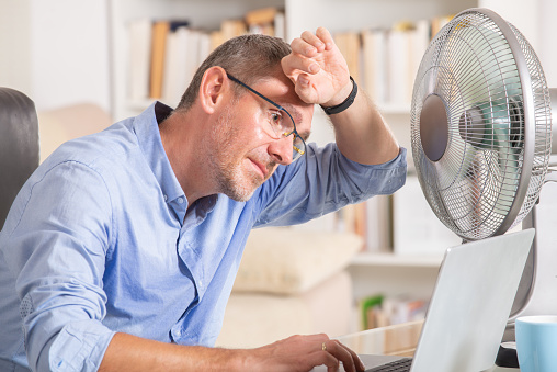Man suffers from heat in the office or at home 1001614892