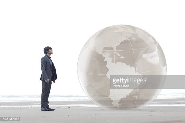 Man suit looking at giant globe on beach
