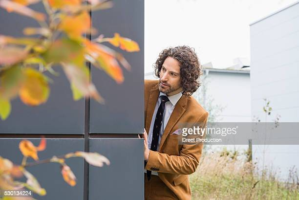 Man suit watching suspicious nosy wall hiding