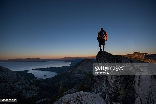 man summiting a beautiful mountain top in lake tahoe - lake tahoe stock photos and pictures