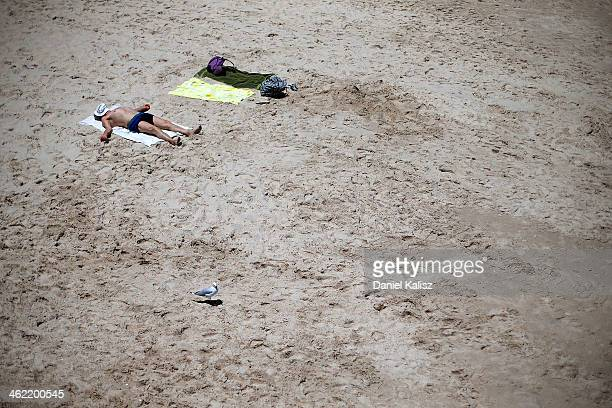 A man sunabathes in the midday sun during a heat wave at Glenelg beach on January 13 2014 in Adelaide Australia Temperatures are expected to be over...