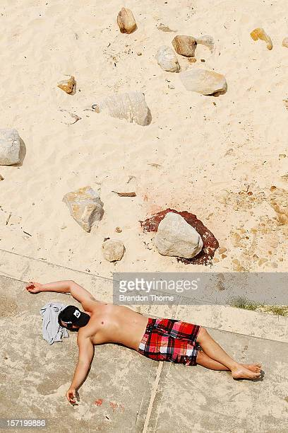 A man sunbakes at Bondi Beach on November 30 2012 in Sydney Australia Temperatures in the high 30s and low 40s are expected to hit parts of the state...