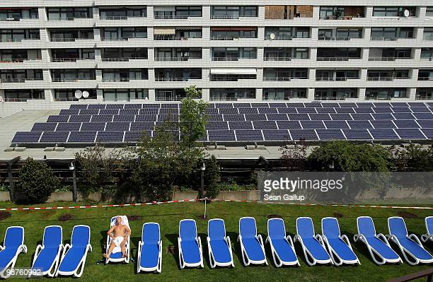 A man sunbathes at a rooftop spa next to solar cell panels on April 30 2010 in Berlin Germany Germany has invested heavily in solar and other...