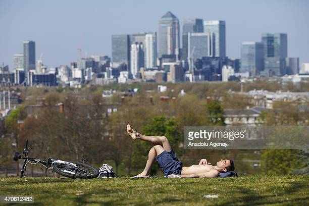 A man sunbathes at Greenwich Park in London England as temperature hits 17C on on April 21 2015