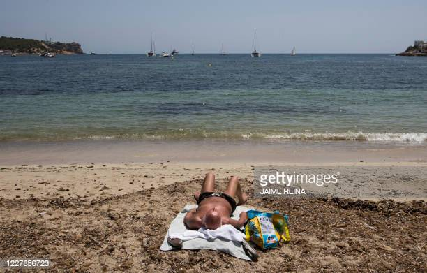A man sunbathes at Talamanca beach in Ibiza on July 31 2020 With Spanish health authorities struggling with a rising number of coronavirus infections...