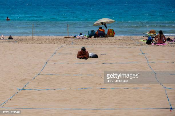 A man sunbathes in a designated ropedoff area on Poniente Beach in Benidorm on June 21 a day after the town's beaches were reopened after three...