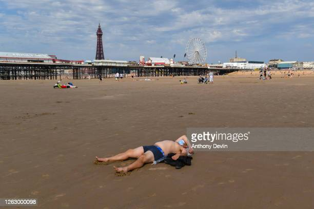 A man sunbathes in a face mask on close to Central Pier on July 31 2020 in Blackpool England High temperatures are forecast across the UK today with...