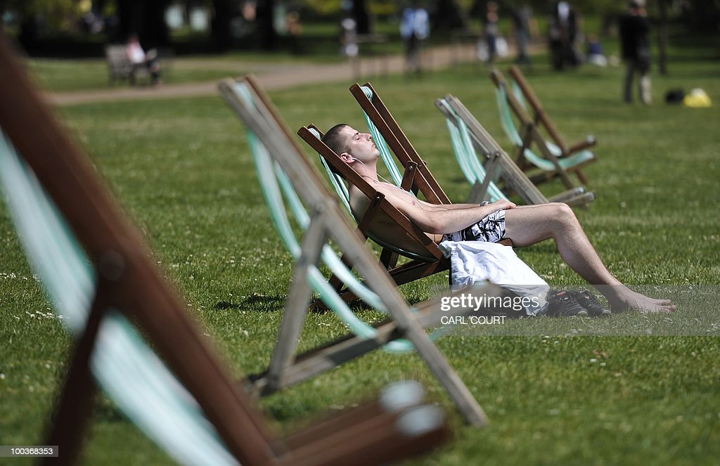 A man sunbathes in St James' Park in London, on May 24, 2010. A mini-heatwave over the last few days has seen UK temperatures outstrip many European holiday destinations such as Rome and Rhodes. AFP PHOTO/Carl Court