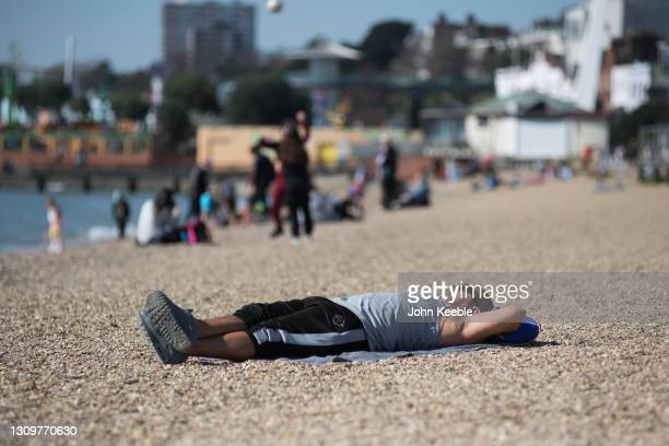 Man sunbathes in the warm weather on the beach on March 29, 2021 in Southend, England. Today the government eased its rules restricting outdoor...