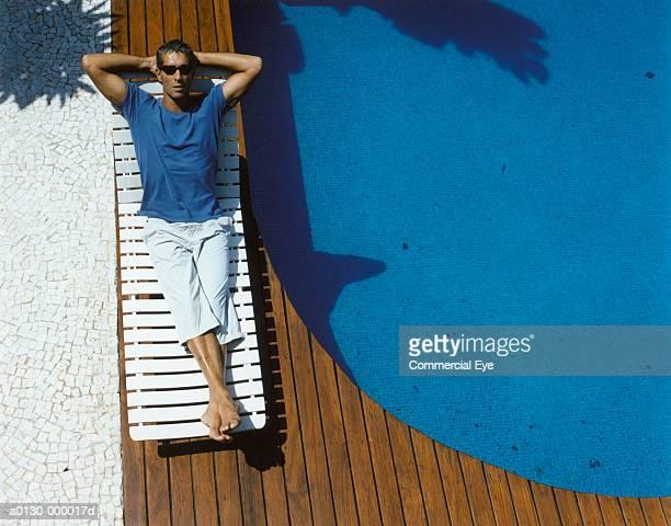 man sunbathes near pool - hände hinter dem kopf stock-fotos und bilder