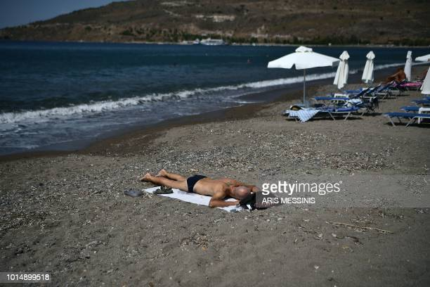 A man sunbathes on a beach in the village of Petra on the Greek island of Lesbos on August 3 2018