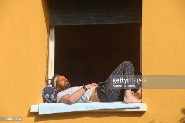 A man sunbathes on the windowsill of his home window on March 22 2020 in Rome Italy As Italy extends its nationwide lockdown to control the spread of...