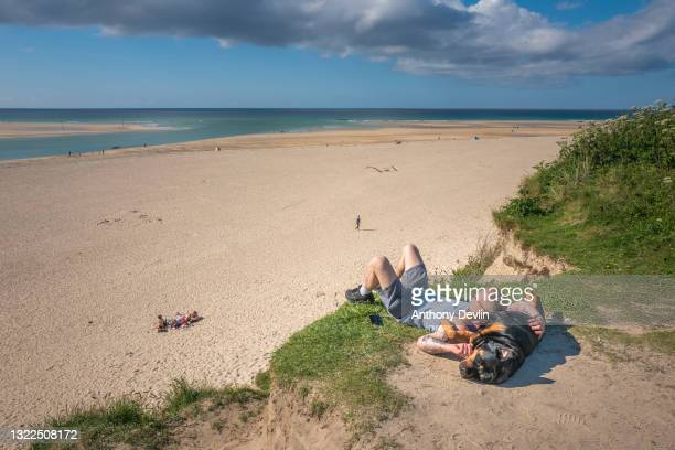 Man sunbathes with a dog on Hayle beach, close to the venue for the G-7 Summit on June 04, 2021 in Carbis Bay, Cornwall. On June 11, Prime Minister...