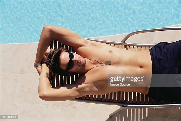 Man sunbathing by the pool