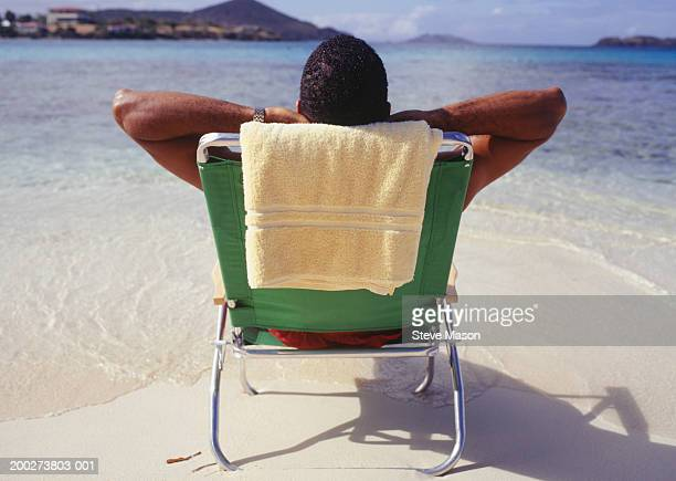 Man sunbathing in deckchair at ocean, rear view