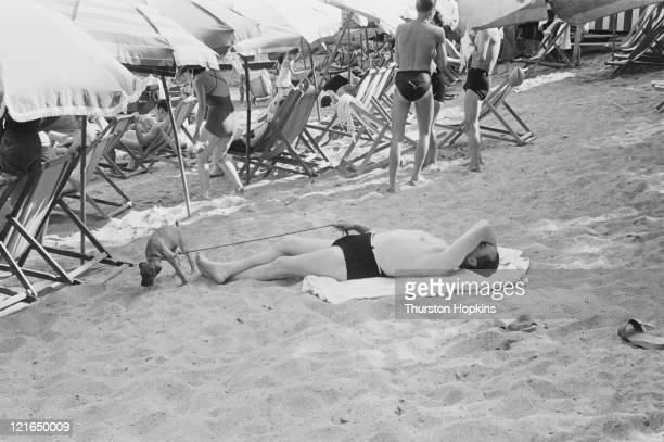 A man sunbathing with his dog on Paraggi Beach near the tourist resort of Portofino Italy August 1952 Original Publication Picture Post 6023 unpub