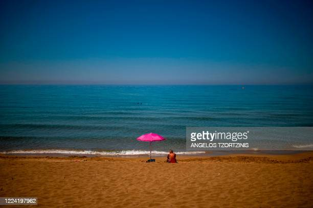 Man sunbaths at the Glyfada beach in the island of Corfu on July 1, 2020 as the island welcomes its first tourists after months of closure due to the...