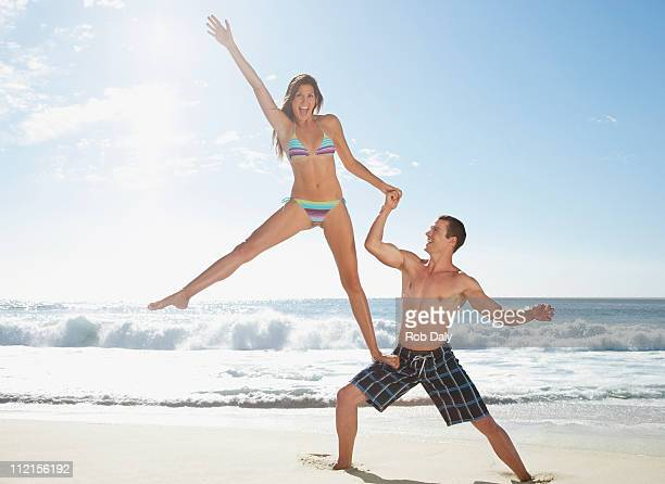 Man supporting girlfriend on his leg at beach