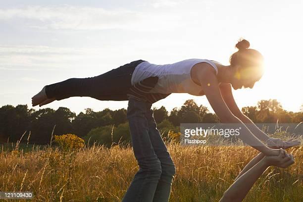 Man supporting woman balancing on his feet