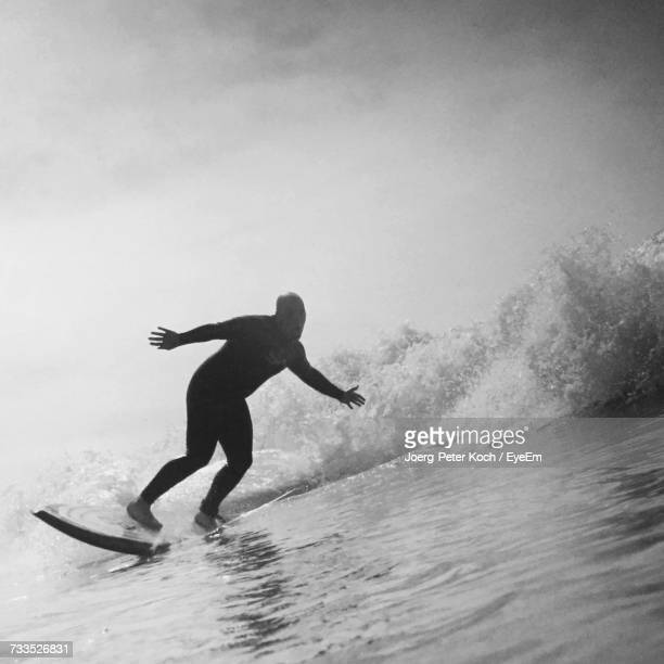 Man Surfing By Waves In Sea