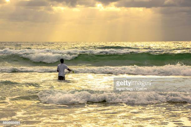 Man Surfing On Sea Against Sky During Sunset