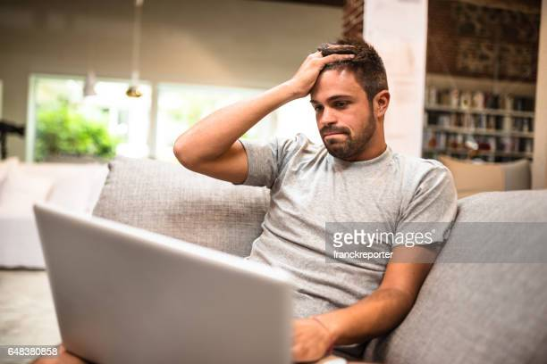 man surfing on the coach and buying on the web