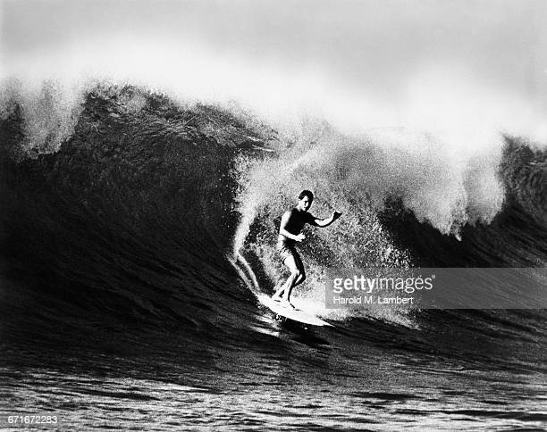 man surfing on wave - number of people stock pictures, royalty-free photos & images