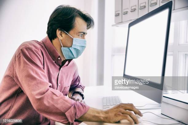 man surfing the internet wearing a facemask. - surfing the net stock pictures, royalty-free photos & images