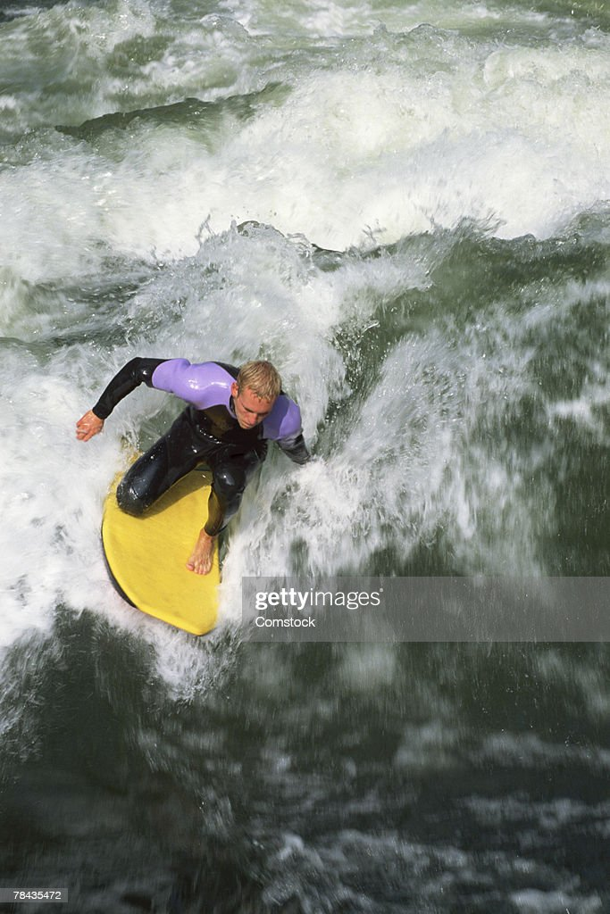 Man surfing wave on boogie board in the Isar River at Munich , Germany : Stockfoto