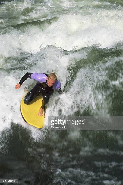 Man surfing wave on boogie board in the Isar River at Munich , Germany