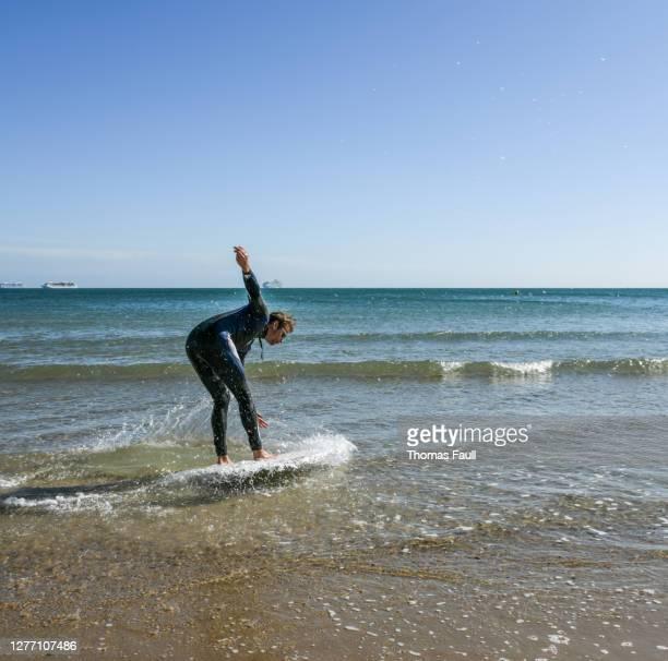 浅瀬のボード上の男のサーフィン - プール湾 ストックフォトと画像