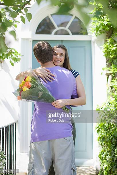 Man surprising girlfriend with bouquet of roses
