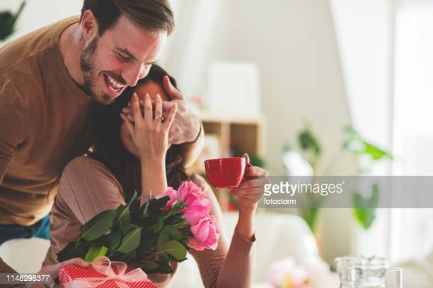 man surprising his girlfriend with flowers - valentine's day stock pictures, royalty-free photos & images