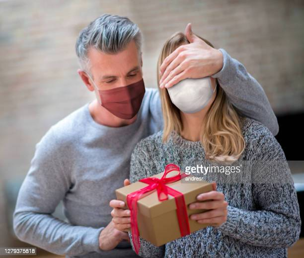 man surprising woman with a christmas gift and wearing a facemask - adulto di mezza età foto e immagini stock