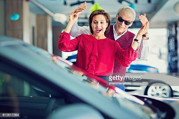 Man surprising woman with a new car