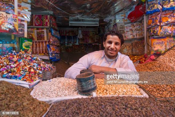 man surrounded by nuts and candy at market, saana, yemen - yemen stock pictures, royalty-free photos & images