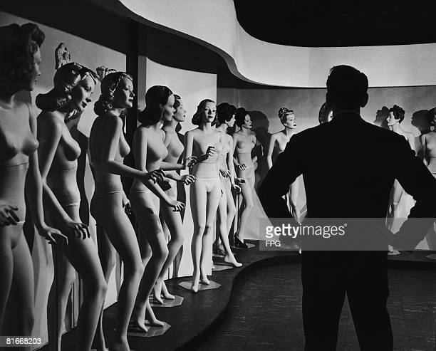 A man surveying a group of mannequins each with a wig in a different hairstyle circa 1935