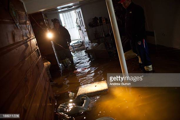 A man surveys the damage to his basement after flooding due to Hurricane Sandy on October 30 in Little Ferry New Jersey The storm has claimed at...