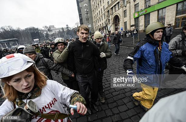 A man suspected of being a sniper and member of the progovernment forces is detained by antigovernment protestors in Kiev on February 22 2014 The...