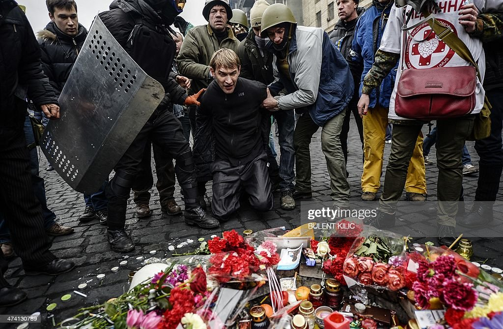 A man (C) suspected of being a sniper and member of the pro-government forces is forced by anti-government protestors to pay his respects to a mourning place of a victim killed in the recent clashes in Kiev on February 22, 2014. The regime of Ukraine's president appeared close to collapse on February 22 as the emboldened opposition took control of central Kiev and key government and parliament positions and voted to immediately free its jailed leader Yulia Tymoshenko.