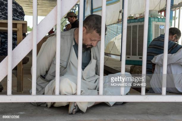 Man suspected of being an Egyptian member of the Islamic State group is detained by Iraqi soldiers at a temporary camp in the compound of the closed...
