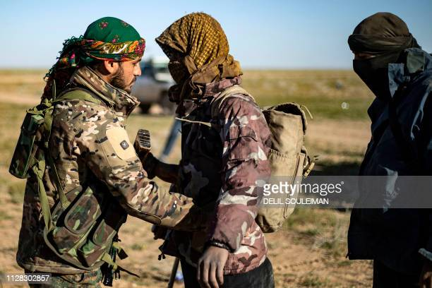 A man suspected of being an Islamic State group fighter waits is searched by members of the Kurdishled Syrian Democratic Forces after leaving the IS...