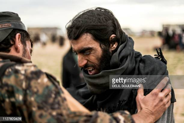 TOPSHOT A man suspected of being an Islamic State group's fighter is searched by a member of the Kurdishled Syrian Democratic Forces after leaving...