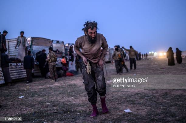 TOPSHOT A man suspected of belonging to the Islamic State group walks past members of the Kurdishled Syrian Democratic Forces just after leaving IS'...